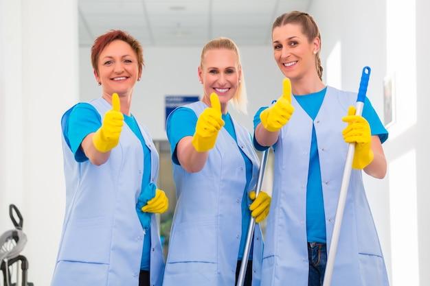 Donne delle pulizie che lavorano in squadra mostrando il pollice in alto segno