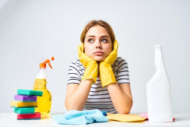 La donna delle pulizie si siede al servizio di lavoro detersivo tavolo.