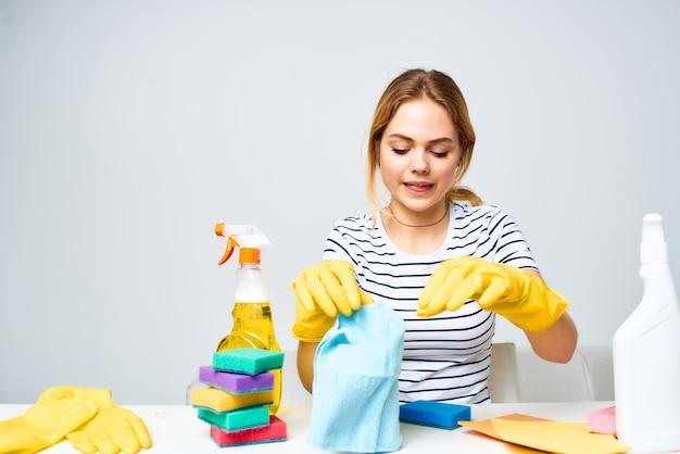 Una donna delle pulizie si siede a un tavolo fornendo servizi di pulizia sfondo chiaro