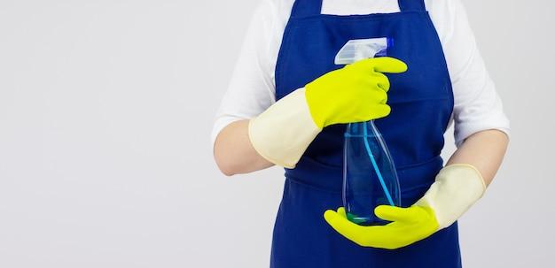 Donna delle pulizie con flacone spray e guanti verdi su sfondo bianco. servizio di pulizia concettuale
