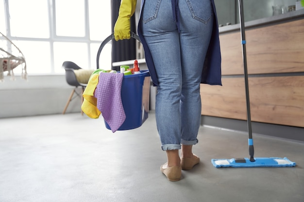 Donna delle pulizie al lavoro. vista posteriore di una donna che tiene mop e secchio o cesto di plastica con stracci, detersivi e diversi prodotti per la pulizia mentre si trova in cucina. lavori domestici, pulizie