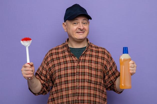 Uomo delle pulizie in camicia a quadri e cappuccio che tiene in mano una bottiglia di prodotti per la pulizia e una spazzola per la pulizia che sembra felice e positiva, sorridente fiduciosa