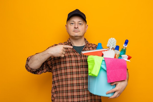 Uomo delle pulizie in camicia a quadri e berretto che tiene il secchio con strumenti per la pulizia