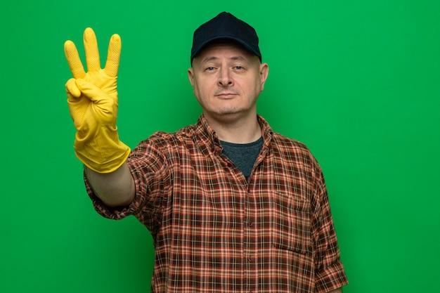 Uomo delle pulizie in camicia a quadri e berretto che indossa guanti di gomma guardando la telecamera sorridendo fiducioso che mostra il numero tre con le dita in piedi su sfondo verde