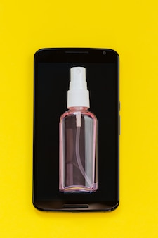 Pulizia dello schermo del telefono con un detergente, spray. concetto di disinfezione. telefono cellulare, cellulare con flacone spray
