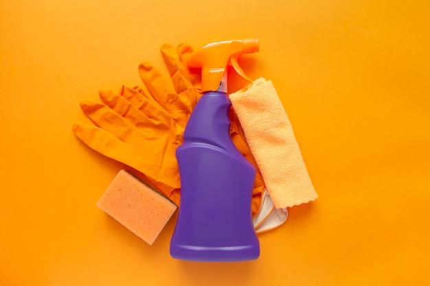 Agente di prodotti per la pulizia, spugne, tovaglioli e guanti di gomma, sfondo arancione.