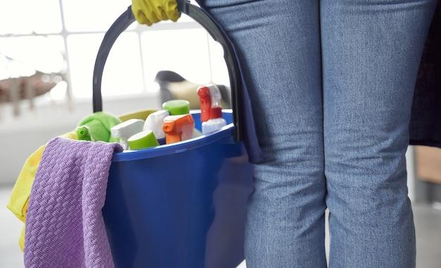 Prodotti per la pulizia. immagine ravvicinata di una donna che tiene in mano un secchio o un cesto di plastica con stracci, detergenti e diversi prodotti per la pulizia durante la pulizia a casa. servizio di pulizia, lavori domestici, pulizie