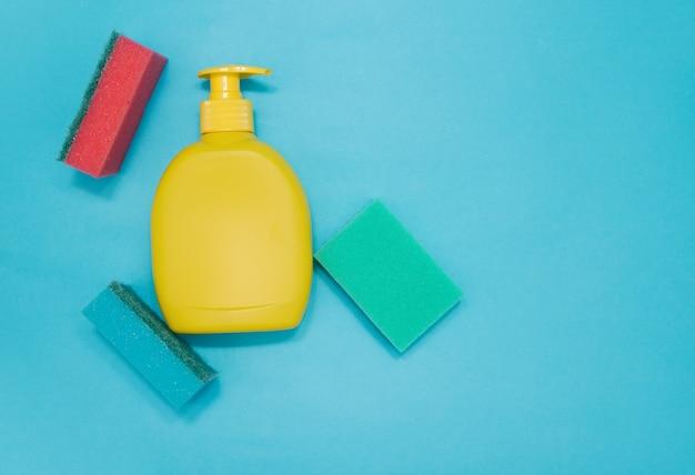 Prodotti per la pulizia e una spugna per lavare i piatti su sfondo blu. spazio per il testo.