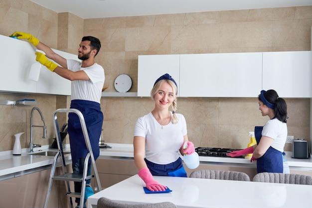 Squadra di servizio di pulizia al lavoro in cucina in casa privata