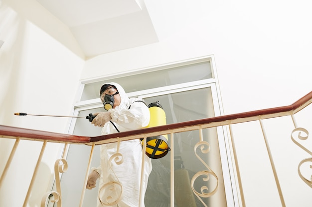 Addetto al servizio di pulizia che disinfetta le scale