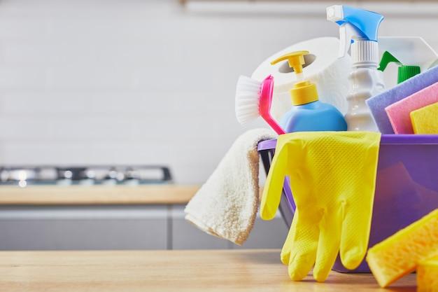 Set di pulizia: spugna, bottiglia, guanto, pennello, spray sul tavolo e grigio