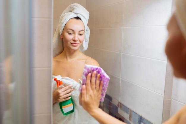 Pulisce nella doccia una bella ragazza lava lo specchio con uno straccio