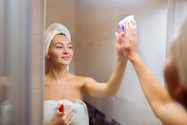 Pulizia nel bagno con doccia. una bella ragazza lava lo specchio con uno straccio.