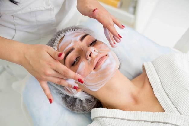 Pulizia della pelle con schiuma, una bella donna nella bellezza del salone di bellezza. lavoro cosmetologo.
