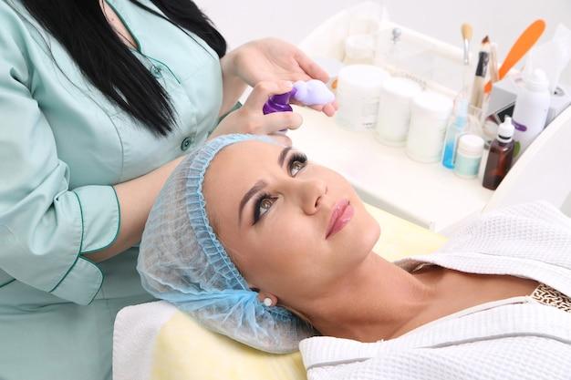 Pulizia della pelle con schiuma, una bella donna nella bellezza del salone di bellezza