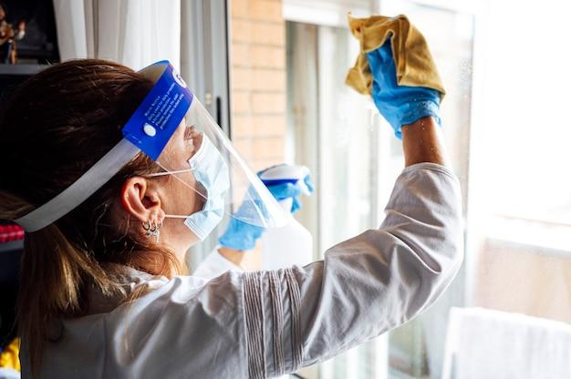 Personale addetto alle pulizie disinfetta la casa dai virus, indossando una mascherina protettiva trasparente