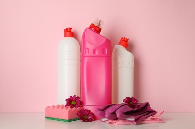Strumenti di pulizia e fiori su sfondo rosa, spazio per il testo