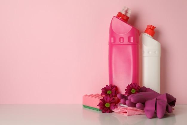 Strumenti di pulizia e fiori sul rosa, spazio per il testo