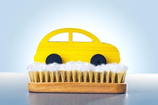 Pulizia dell'auto giocattolo gialla su sfondo blu. concetto di autolavaggio.
