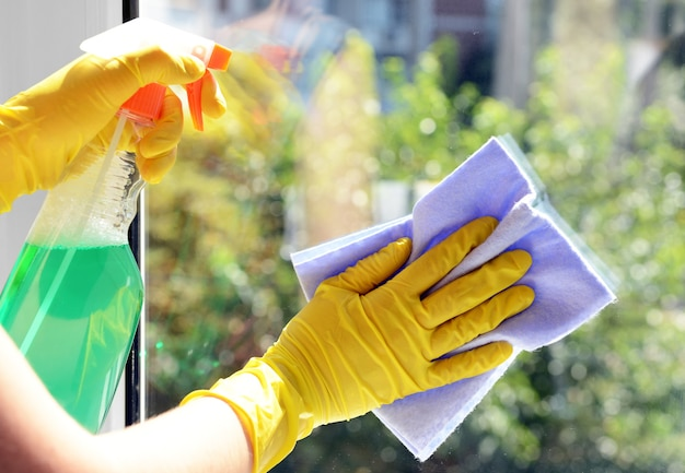 Pulizia delle finestre con uno straccio e un detergente speciali