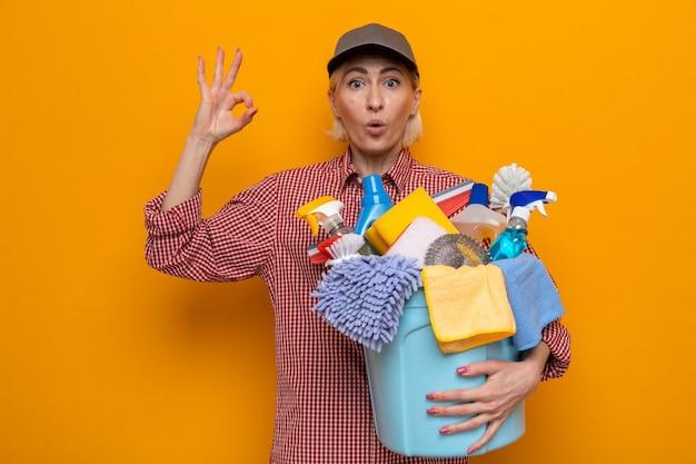 Donna delle pulizie in camicia a quadri e cappello che tiene il secchio con strumenti per la pulizia che guarda la telecamera che mostra il segno ok in piedi su sfondo arancione