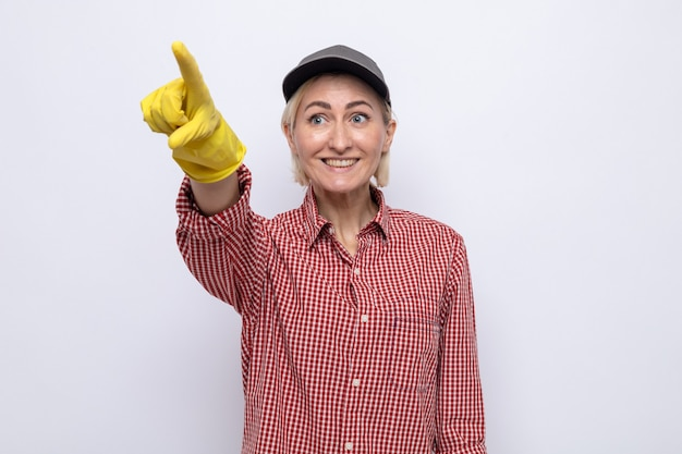 Donna delle pulizie in camicia a quadri e berretto che indossa guanti di gomma che guarda da parte felice e positivo indicando con il dito indice qualcosa