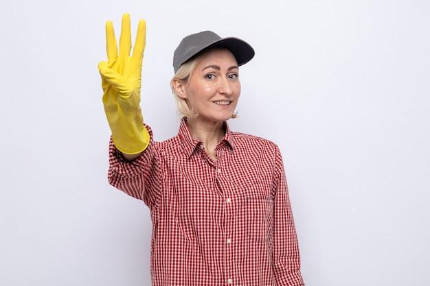 Donna delle pulizie in camicia a quadri e berretto che indossa guanti di gomma guardando la fotocamera con un sorriso sul viso che mostra il numero tre con le dita in piedi su sfondo bianco