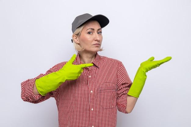 Donna delle pulizie in camicia a quadri e berretto che indossa guanti di gomma che sembra sicura di sé e si presenta con il braccio della mano puntato con l'indice sul braccio