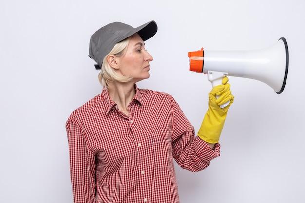 Donna delle pulizie in camicia a quadri e berretto che indossa guanti di gomma guardando il megafono con una faccia seria