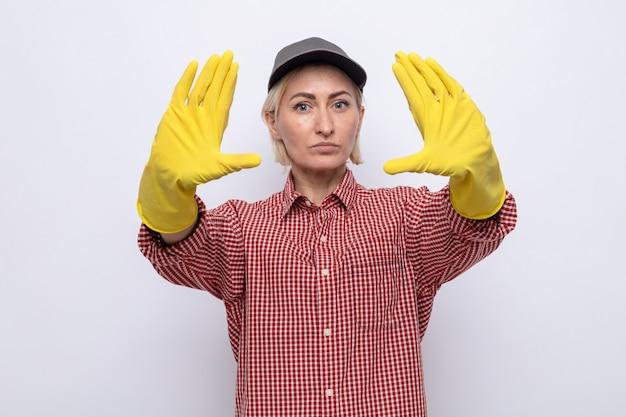 Donna delle pulizie in camicia a quadri e berretto che indossa guanti di gomma che guarda con una faccia seria che fa un gesto di arresto con le mani