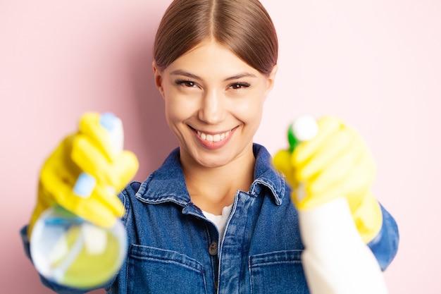 Operaio delle pulizie in tuta, guanti gialli e prodotti per la pulizia