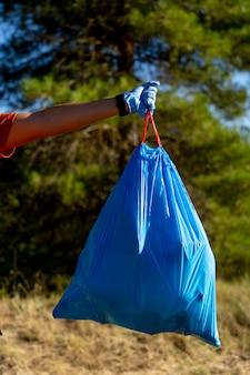 Operaio delle pulizie che lavora nel bosco raccogliendo spazzatura.