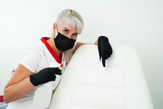 Pulizia del posto di lavoro nel salone di bellezza della spa una giovane donna con maschera protettiva e guanti tiene...