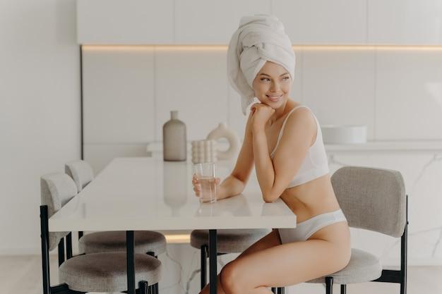 Corpo purificante dalle tossine. giovane bella donna europea in biancheria intima bianca e asciugamano avvolto sulla testa che si rilassa dopo la doccia mattutina, tenendo in mano un bicchiere di acqua pura mentre è seduto al tavolo in cucina