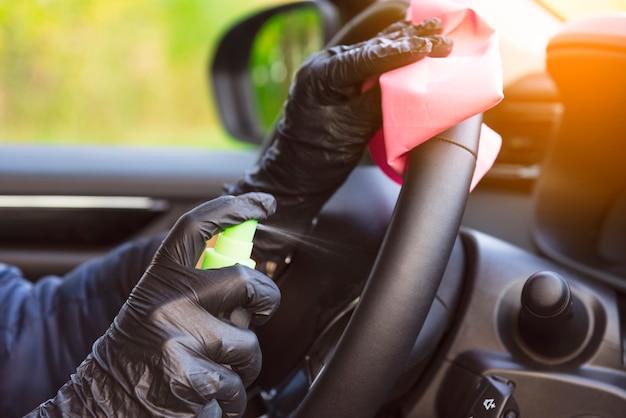 Detergere l'interno dell'auto e spruzzare con liquido disinfettante. mani in guanti protettivi in gomma disinfettanti all'interno per la protezione dalle malattie virali.