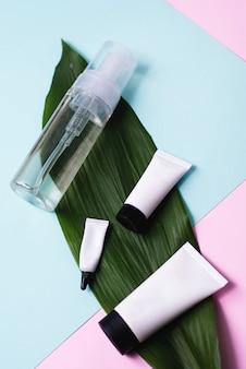 Schiuma detergente o acqua micellare e una varietà di motivi per creme su una foglia di palma