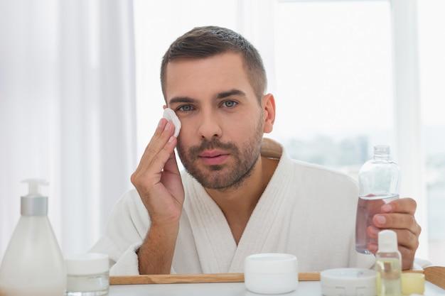 Lozione detergente. bel uomo serio che pulisce la sua pelle durante l'utilizzo di una lozione detergente