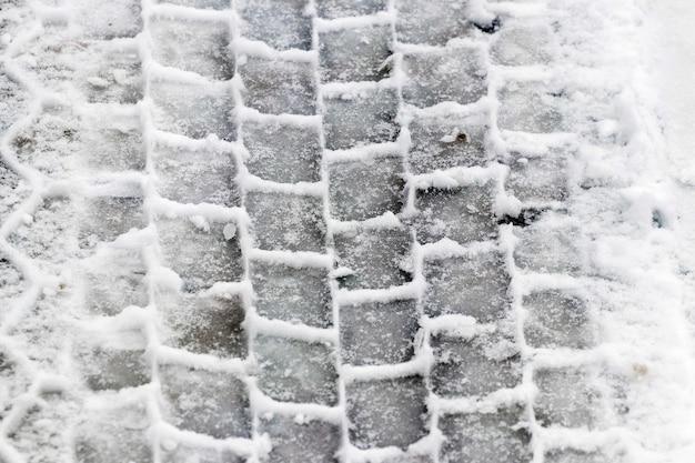Impronta chiara di un pneumatico per auto sulla neve bagnata
