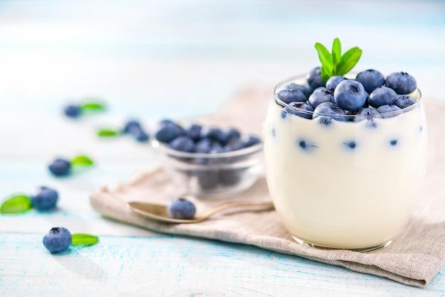 Chiaro barattolo di yogurt con i mirtilli più su fondo di legno