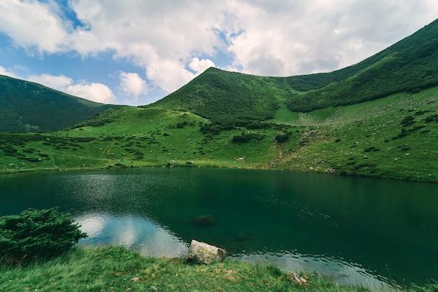 Lago limpido sullo sfondo di montagne verdi e cielo blu in condizioni di sole estivo. turismo, ricreazione, arrampicata.