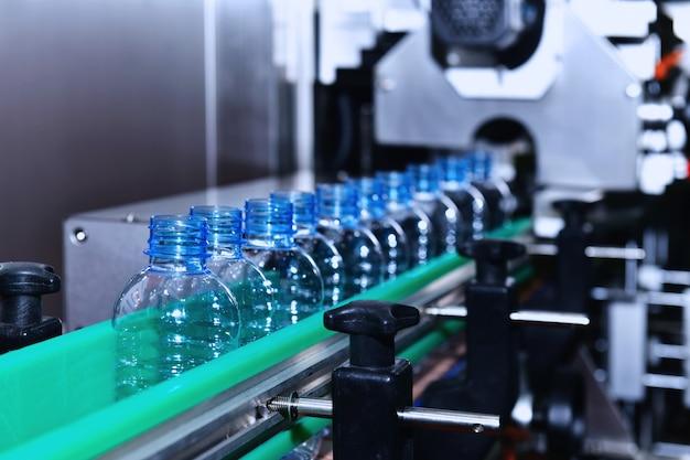 Trasferimento bottiglie in plastica trasparente su sistemi di trasporto automatizzati industriali per imballi