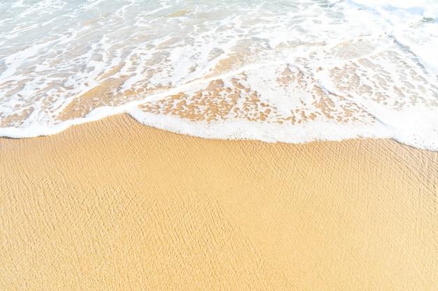 Spiaggia di sabbia chiara e schiuma d'onda sulla spiaggia con copia spazio per lo sfondo