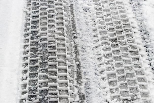 Tracce evidenti di pneumatici per auto sulla neve durante il disgelo, strada scivolosa