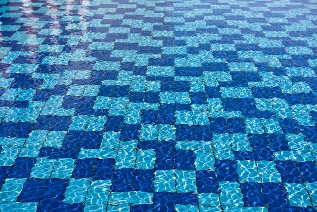 Fondo trasparente dell'acqua della piscina. riflessi del sole nell'acqua della piscina dall'alto Foto Premium