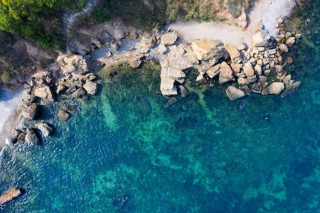 Acqua limpida sulla spiaggia con rocce, vista aerea.
