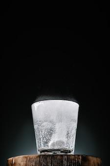 Acqua limpida in un bicchiere con vitamina c, primo piano, parete scura con spazio di copia, messa a fuoco selettiva. l'acqua bolle dalla dissoluzione della compressa effervescente. assunzione di vitamine, prevenzione della salute