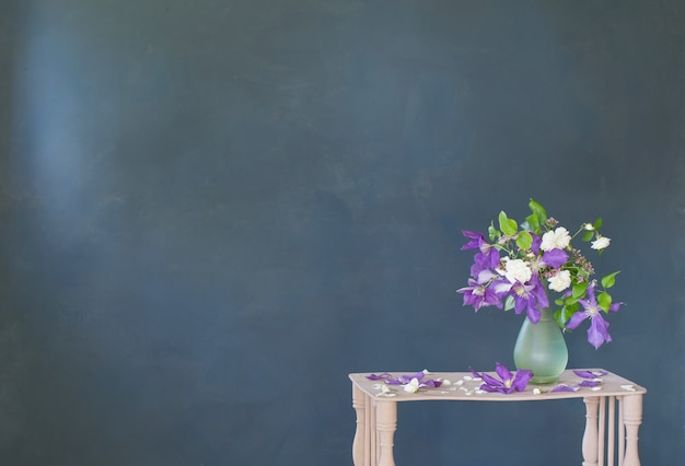 Fiori di clematide in vaso di vetro su mensola in legno d'epoca