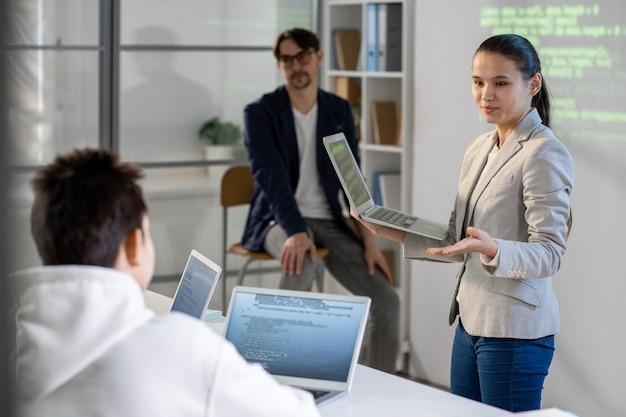 Ragazza intelligente con il computer portatile che risponde alla domanda del compagno di classe mentre fa la presentazione del suo progetto a lezione o conferenza