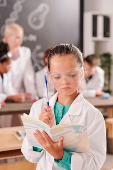 Allievo intelligente della scuola secondaria in camice bianco e occhiali guardando le sue note in quaderno su compagni di classe e insegnante che lavora a lezione