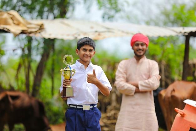Scolaro intelligente che tiene in mano un trofeo vincente e in piedi con suo padre